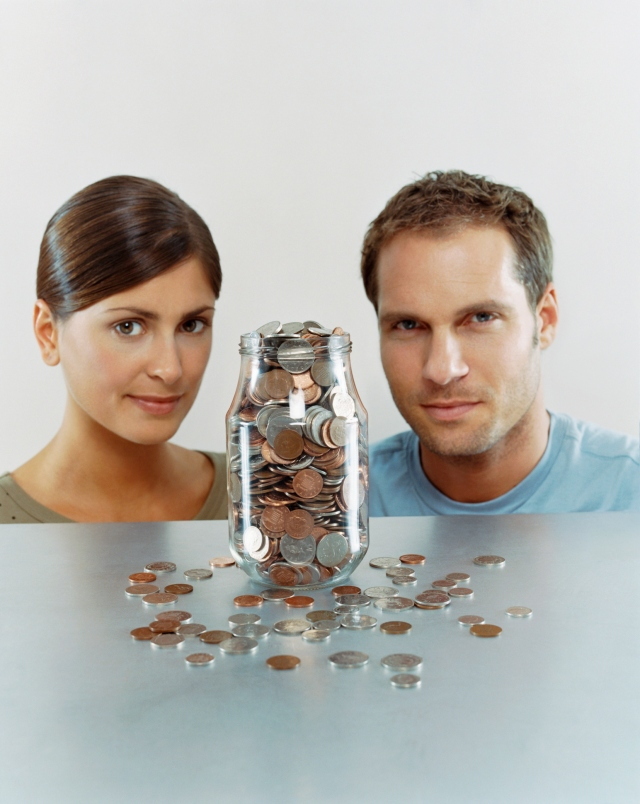 Couple Sitting at a Table With a Jar Full of Coins in Front of Them